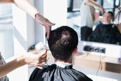 O close-up, o cabeleireiro mestre faz o penteado e o estilo com tesouras e pente Barbeiro do conceito imagens de stock