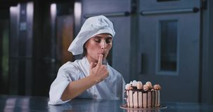 O close up carismático da senhora da padaria à câmera toma algum creme do bolo com dedo e gosto ela que veste um cozinheiro chefe video estoque