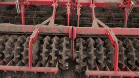 O close-up, cultivador do trator cultiva, escava o solo O trator ara o campo Rebento automatizado para o solo de escava??o dentro video estoque