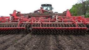 O close-up, cultivador do trator cultiva, escava o solo O trator ara o campo Rebento automatizado para o solo de escava??o dentro filme