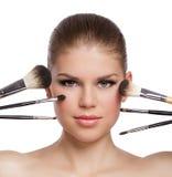 O close-up da beleza da mulher loura lindo nova com composição escova perto de sua cara imagem de stock
