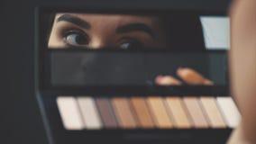 O close-up da cara de uma jovem mulher obtém uma composição Uma mulher bonita que aplica uma sombra para os olhos em suas sobranc video estoque
