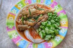 O close-up da farinha de arroz adiciona a água, o caril vermelho, os pés de galinha, vegetais verdes frescos, o alimento tailandê foto de stock
