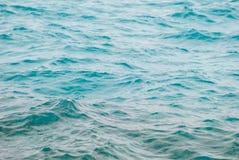 O close up da foto da superfície clara bonita da água do oceano do mar de turquesa com ponto baixo das ondinhas acena no fundo do Fotografia de Stock