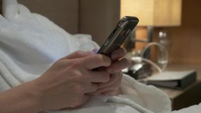 O close up da jovem mulher entrega os sms de datilografia que enrolam imagens do telefone as m?os f?meas usam um smartphone na no video estoque