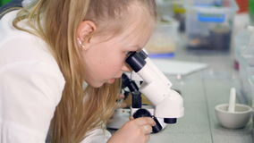 O close-up da menina que olha a amostra no microscópio 4K