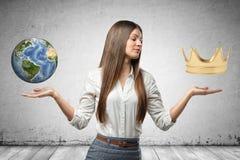 O close-up da mulher de negócios nova, cotovelos dobrou-se, as mãos nos lados que enfrentam acima, a pouca terra e coroa do ouro  imagem de stock