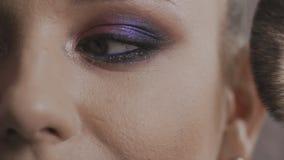 O close-up da mulher que aplica o cosmético com grande compõe a escova no lento-mo video estoque