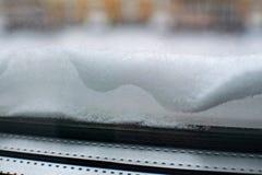 O close-up da neve encontra-se na soleira fora Neve na soleira no inverno, janela coberto de neve fotografia de stock royalty free