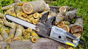 O close up da serra de cadeia encontra-se no fundo de logs vistos da noz Fotografia de Stock