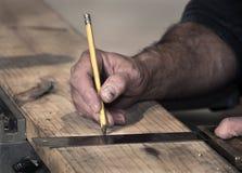 O close up das mãos ásperas do ` s do carpinteiro usando um lápis e um quadrado velho para marcar uma linha em uma placa de madei fotografia de stock
