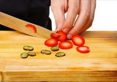 O close-up das mãos do ` s do cozinheiro chefe cortou em uma grande faca da morango fotos de stock