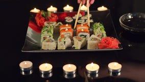 O close-up das mãos dos homens e as mulheres comem o sushi filme