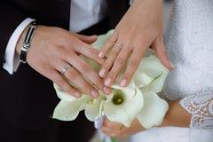 O close-up das mãos dos recém-casados com alianças de casamento, toca delicadamente no ramalhete do casamento das flores foto de stock