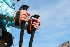 O close-up das mãos fêmeas com trekking cola para o nordic que anda na perspectiva do lago alpino e distante Foto de Stock