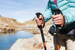 O close-up das mãos fêmeas com trekking cola para o nordic que anda na perspectiva do lago alpino e distante Fotos de Stock Royalty Free