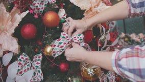 O close-up das mãos fêmeas decora a árvore de Natal Foto de Stock Royalty Free