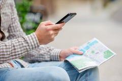 O close up das mãos masculinas que guardam o telefone celular e a cidade traçam fora na rua Homem que usa o smartphone móvel para Foto de Stock Royalty Free