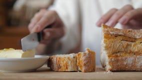 O close-up das mãos das mulheres com uma faca cortou o pão e espalhou a manteiga nele filme