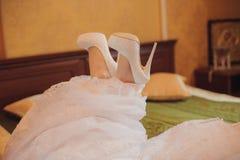 O close-up das sapatas de uma noiva está encontrando-se na cama Fotografia de Stock