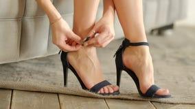 O close-up de botões da jovem mulher trava sapatas dos saltos altos Movimento lento Assento no sof? em casa video estoque