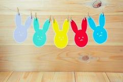 O close-up de coelhos de papel coloridos mostra em silhueta os quadros que penduram em um cabo contra o fundo de madeira Fotografia de Stock Royalty Free