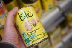 O close up de cogumelos naturais enlata à disposição em Cora Supermarket Fotografia de Stock Royalty Free
