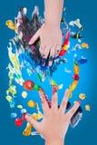 O close up de crianças pequenas entrega fazer a pintura de dedo Foto de Stock