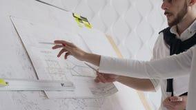 O close-up de dois arquitetos que discutem um projeto construir um projeto novo descreveu desenhos de que são descritos na filme