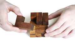 O close up de equipa as mãos que montam o cubo de madeira Foto de Stock Royalty Free