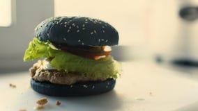O close up de hamburgueres feitos profissionais do preto da carne com alface e maionese serviu na placa de corte filme