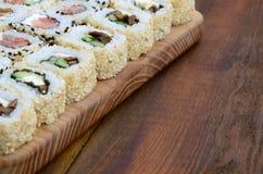 O close-up de muitos rolos de sushi com enchimentos diferentes encontra-se em uma superfície de madeira Tiro macro do alimento ja Fotografia de Stock Royalty Free