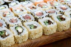 O close-up de muitos rolos de sushi com enchimentos diferentes encontra-se em uma superfície de madeira Tiro macro do alimento ja Foto de Stock Royalty Free