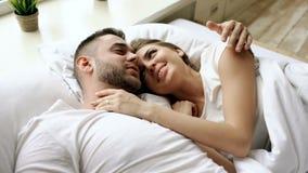 O close up de pares bonitos e loving novos fala e abraça na cama ao acordar na manhã video estoque