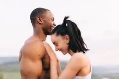 O close-up de pares 'sexy' da raça misturada do ajuste com os corpos perfeitos no sportswear que abraçam levemente em montanhas a Imagem de Stock