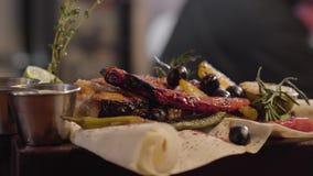 O close up de peixes grelhados dos salmões serviu com os molhos, as ervas, as azeitonas, a pimenta de pimentão, o cal e o limão e filme