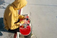 O close-up de um adolescente vestiu-se em calças de brim de uma camiseta e as sapatilhas que sentam-se em um patim estacionam gua imagens de stock royalty free
