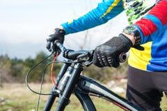 O close-up de um ciclista do mtb do piloto do homem da mão em luvas do esporte que prepara-se para uma raça guarda firmemente o v fotografia de stock royalty free