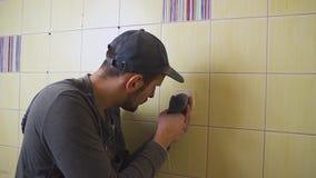 O close-up de um eletricista com uma chave de fenda que seting acima de uma tomada branca, o conceito da eletrificação da sala é vídeos de arquivo