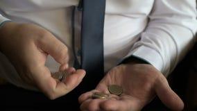O close up de um homem de negócios entrega a contagem de moedas na tabela filme