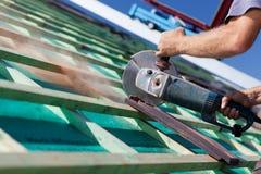 O close-up de um roofer que usa uma circular da mão considerou Fotografia de Stock Royalty Free