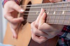 O close-up de um ` s da jovem mulher entrega o jogo da guitarra Imagens de Stock Royalty Free
