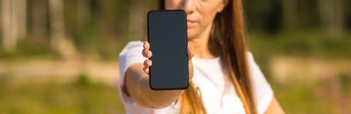 O close-up de um smartphone, uma menina está guardando um telefone na mão em um fundo borrado fotos de stock royalty free