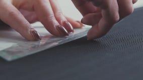 O close-up de uma costureira que leva a cabo uma linha para esboçar veste-se atelier vídeos de arquivo