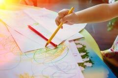 O close-up de uma criança pequena tira lápis coloridos fotografia de stock royalty free