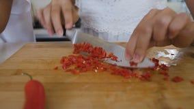 O close-up de uma fêmea entrega o corte da pimenta encarnado na placa de corte em casa na cozinha As mãos fêmeas estão cortando o filme
