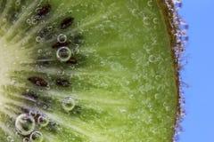 O close up de uma fatia do quivi coberta na água borbulha contra um fundo do azul do aqua Fotografia de Stock Royalty Free