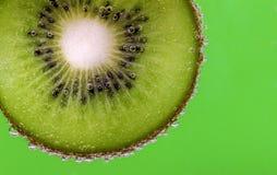O close up de uma fatia do quivi coberta na água borbulha contra um fundo verde Fotografia de Stock