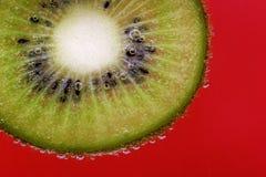 O close up de uma fatia do quivi coberta na água borbulha contra um fundo vermelho Imagem de Stock Royalty Free