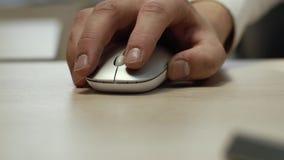 O close-up de uma m?o do homem usa o rato sem fio branco A c?mera vai acima vídeos de arquivo